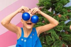 Flickan satte stora julbollar till hennes ögon royaltyfri foto