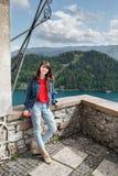 Flickan ser bergsikterna dalsikt och sjö på fjällängar bakgrunden Arkivfoto