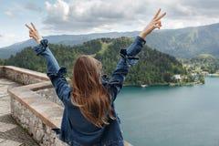 Flickan ser bergsikterna dalsikt och sjö på fjällängar bakgrunden Dra tillbaka till kameran Royaltyfria Foton