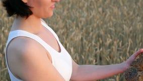 Flickan ser brödet och ler Doftande bröd på bakgrunden av ett vetefält Skörd och jordbruk arkivfilmer