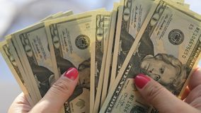 Flickan ser de nya tjugo dollarräkningarna i hennes händer, royaltyfria foton