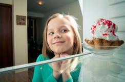 Flickan ser den söta kakan Royaltyfri Bild