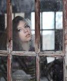 Flickan ser det gamla fönstret royaltyfria foton