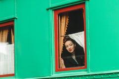 Flickan ser ett gammalt järnväg vagnsfönster Arkivfoton