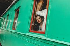 Flickan ser ett gammalt järnväg vagnsfönster Fotografering för Bildbyråer
