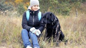 Flickan ser försiktigt hennes hund HD royaltyfri bild