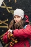 Flickan ser hennes klocka som väntar på någon Royaltyfri Foto