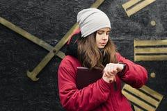 Flickan ser hennes klocka som väntar på någon Fotografering för Bildbyråer