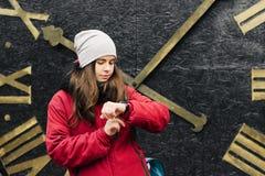 Flickan ser hennes klocka som väntar på någon Royaltyfri Fotografi