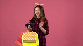 Flickan ser in i shoppingpåsar, därefter som handväskan har kört ut ur pengar, men det finns ett kort Rosa bakgrund långsam rörel stock video