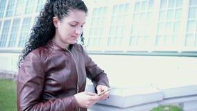 Flickan ser kameran därefter på telefonen i henne händer stock video