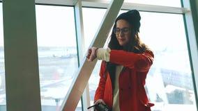 Flickan ser klockan i flygplatsterminalen stock video