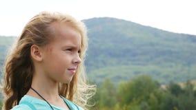 Flickan ser länge in i avståndet och kommer med kikare till hennes ögon fladdrande hårwind stock video