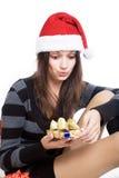Flickan ser med överraskning på julasken som isoleras på vit bakgrund Royaltyfria Bilder
