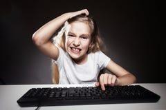 Flickan ser med besvikelse till datoren Royaltyfria Bilder