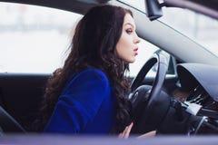 Flickan ser pensively in i vindrutan av bilen Royaltyfria Foton