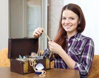 Flickan ser smycken i skattbröstkorg Arkivbild