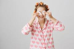 Flickan ser som främling, medan torka av mascara Stående av den roliga känslobetonade kvinnan i papiljotter och pyjamas med hjärt Arkivfoton