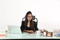Flickan ser tidskriften och bärande svarta exponeringsglas Royaltyfri Foto