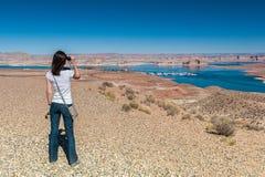 Flickan ser till och med binoсulars på sjön i öknen Royaltyfri Bild