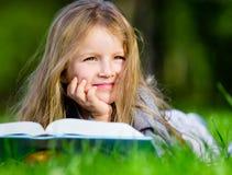 Flickan ser till och med boken som ligger på det gröna gräset royaltyfria foton