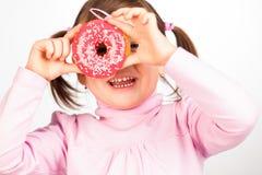 Flickan ser till och med donuts Royaltyfria Foton