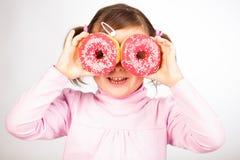 Flickan ser till och med donuts Arkivbild