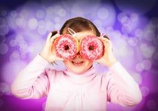 Flickan ser till och med donuts Royaltyfri Bild