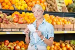 Flickan ser till och med shoppinglista nära högen av frukter arkivbild