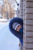 Flickan ser ut bakifrån huset Royaltyfri Foto