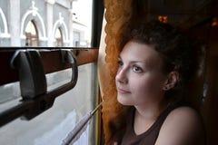 Flickan ser ut drevfönstret på stationen av staden royaltyfria bilder