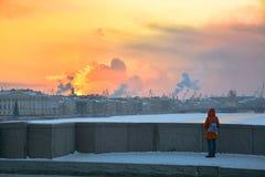 Flickan ser vintersolnedgång från en bro i St Petersburg Royaltyfria Bilder