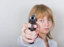 Flickan siktar en pistol royaltyfri foto