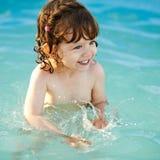 Flickan simmar i pölen royaltyfri bild