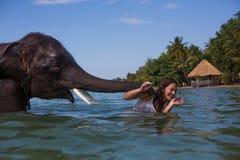 Flickan simmar med elefanten royaltyfria foton