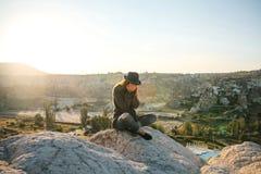 Flickan sitter överst av en kulle och skrik arkivfoton
