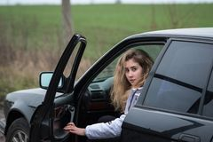 Flickan sitter bak hjulet i bilen och vänder omkring Royaltyfria Foton