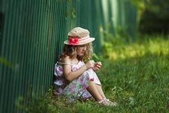 Flickan sitter benägenhet mot ett staket arkivbilder