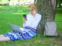 Flickan sitter gräs med anteckningsboken Fördelar för ockupation för försäljningschef Kvinnan med bärbara datorn parkerar in best arkivfoton