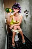 Flickan sitter i en toalett Royaltyfria Foton