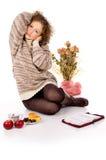 Flickan sitter i en tröja och en bok Arkivfoto