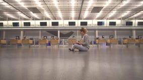 Flickan sitter i terminalen på golvet av flygplatsarbetena med en bärbar dator, medan vänta på flyget lager videofilmer