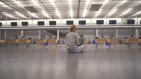 Flickan sitter i terminalen p? golvet av flygplatsarbetena med en b?rbar dator, medan v?nta p? flyget arkivfilmer