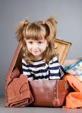 Flickan sitter joyfully i en gammal resväska Royaltyfri Foto