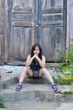 Flickan sitter kliver på nära en gammal dörr Royaltyfri Bild