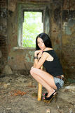Flickan sitter med ett baseballslagträ Arkivfoto