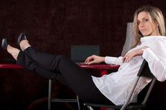 Flickan sitter med foots på en tabell Arkivfoto