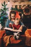 Flickan sitter med hennes lilla syster som läser en sagaafton Royaltyfri Fotografi