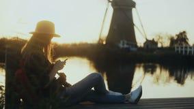 Flickan sitter med smartphonen på solnedgångsjökajen Kvinna som utomhus använder mobil app Traditionellt holländskt väderkvarnlan arkivfilmer