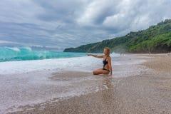 Flickan sitter nära havet och ser de enorma vågorna royaltyfri fotografi